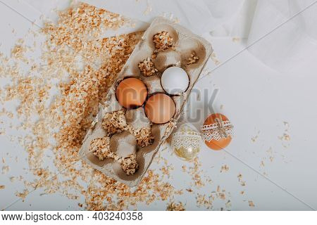 Easter Eggs In Carton Box On White Background With Sawdust Around. Easter Eggs With Lace Border Arou