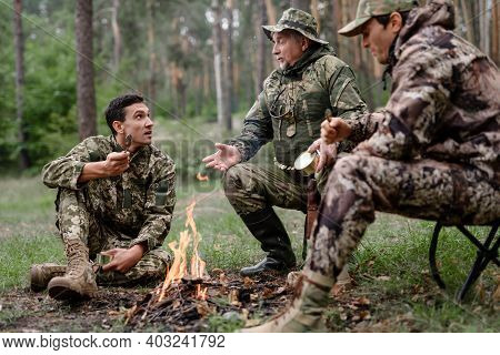 Hunters At Camp Fire Men Have Food And Talk.