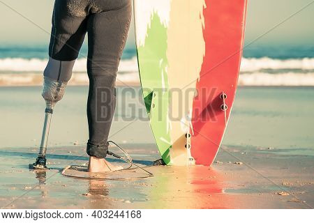 Back View Of Unrecognizable Amputee Standing With Surfboard On Beach. Handicapped Man With Amputated