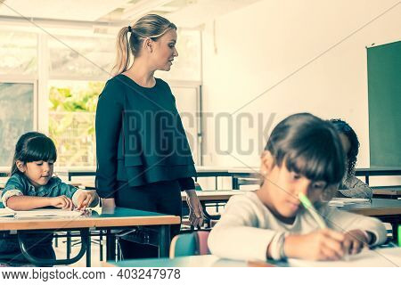 Serious Female Teacher Watching Primary Schoolkids Doing Their Task In Class, Sitting At Desks And W