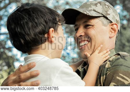 Joyful Father Holding Little Son In Arms, Hugging Boy Outdoors After Returning From Military Mission