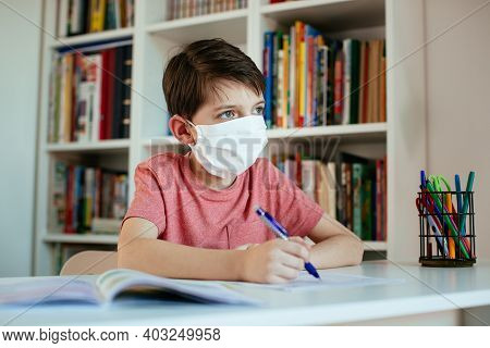 Child Wearing Face Mask Self-studying At Home During Coronavirus Outbreak. Young Student Wearing Sur