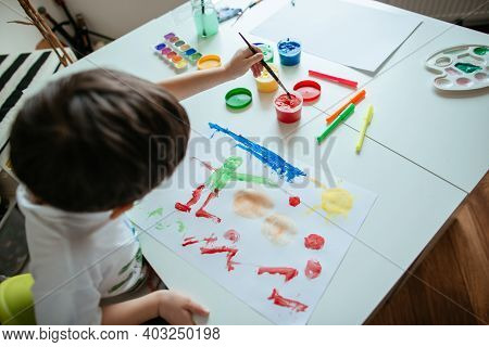 Left Handed 5 Year Old Boy Reaching For Red Paint With Paintbrush. Top View Of Child With Paintbrush