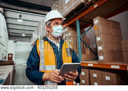Portrait Of A Male Worker Working At Warehouse With Digital Tablet Wearing Safety Mask At Storehouse