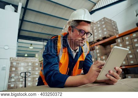 Male Factory Engineer Wearing Spectacles Using Digital Tablet Leaning On Table