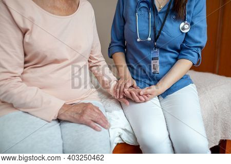 Close Up Of Home Caregiver Holding Hands Of Elderly Woman Patient. Female Nurse Sitting On Hospital