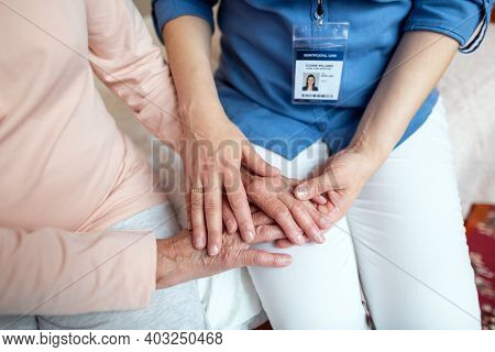Close Up Of Home Nurse Holding Hands Of Senior Woman Patient. Top View Of Female Home Caregiver And