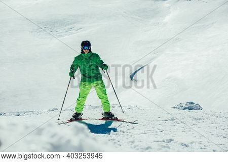 Young Athlete Freestyle Skier Having Fun While Running Downhill In Beautiful Landscape On Sunny Day