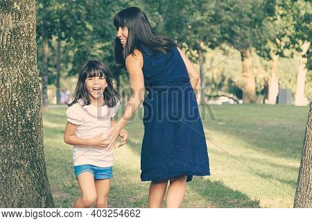 Excited Happy Girl Playing Active Games With Her Mom Outdoors, Standing By Trees In Park And Laughin