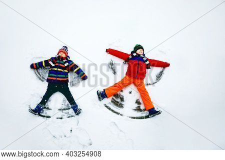 Two Little Siblings Kid Boys In Colorful Winter Clothes Making Snow Angel, Laying Down On Snow. Acti