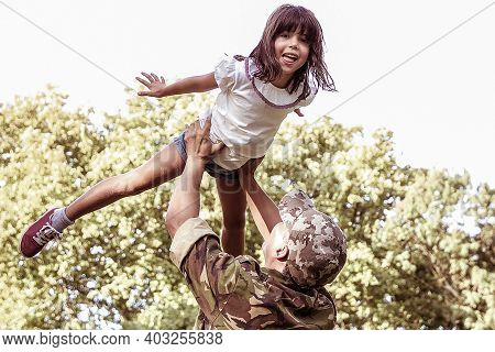 Happy Little Girl Playing With Dad In Military Uniform. Back View Of Father Rising Up His Daughter.