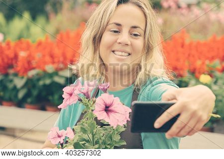 Happy Female Gardener Taking Selfie With Potted Petunia. Caucasian Pretty Blonde Woman Holding Smart
