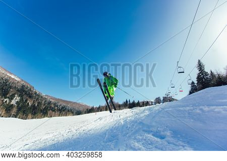 Skier In Mountains. Professional Skier Athlete Skiing Of Ski Resort.winter Vacation And Sport Concep