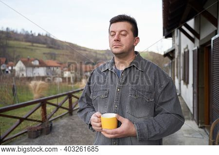 Tall Man In Grey Shirt With Closed Eyes Holding Cup. Slowing Down Concept. The Break During The Work