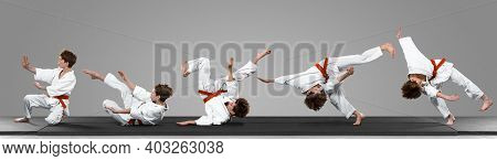 Young Judo Caucasian Male Fighter In White Kimono With Red Belt In Motion, Action During Training. P