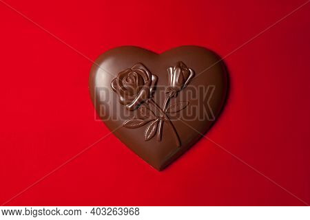 Chocolates Heart Shaped With A Pattern Of Flowers On Red Silk