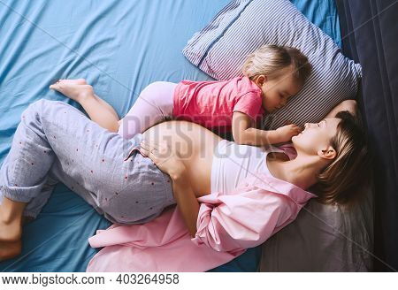 Pregnant Mother With Her Little Daughter Relaxing In Bed. Second Pregnancy. Maternity And Parenting