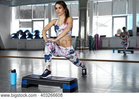 Sporty Woman Doing Lunges With Step. Photo Of Muscular Woman In Fashionable Sportswear On Gym. Stren