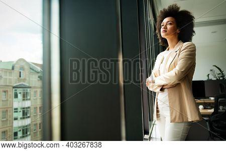 Beautiful African Business Woman Looking Outside Window In Office