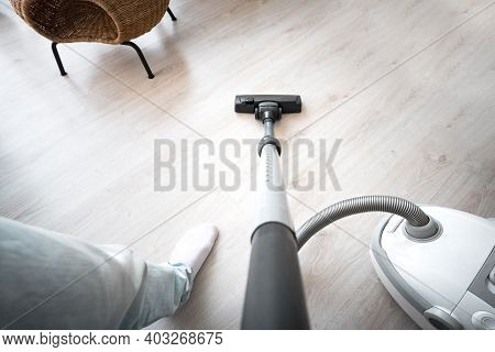 Man Cleaning Floor With Vacuum Cleaner At Home. House Keeping Concept. First-person View