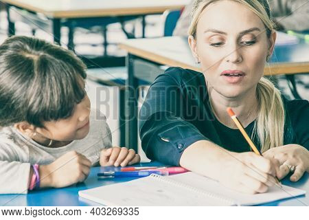 Focused Female Primary School Teacher Helping Girl To Do Task, Writing Or Drawing In Her Copybook An