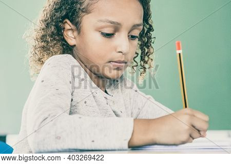 Focused African American Primary School Girl Sitting At Desk And Writing In Pencil. Education Or Bac