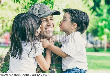Caucasian Man Holding Kids And Smiling. Happy Cute Children Hugging And Kissing Middle-aged Father I
