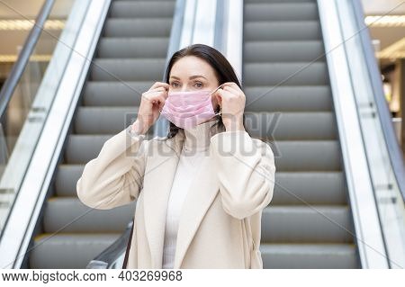 Beautiful Woman Putting On Pink Medical Mask On Her Face Against The Background Of The Escadator In