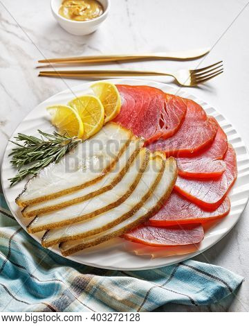 Smoked Fish Platter: Cold Smoked Halibut And Cold Smoked Tuna Slices Served On A White Plate With Ro