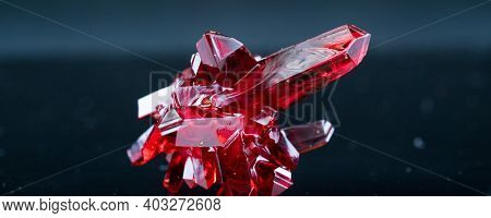 red crystal of natural origin. close up of crystals in ruby color on black background