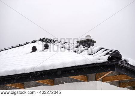 The Roof Of A Single-family House Is Covered With Snow Against A Cloudy Sky, Visible Ridge Tile, Sys