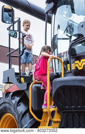 Slovakia 2019, Nitra. Children Play On The New Large Red Tractor At The Exhibition.agricultural Tech
