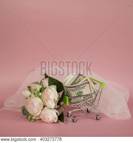 Decorative grocery cart filled with USD banknotes next to bouquet of flowers and Wedding Veil on pin