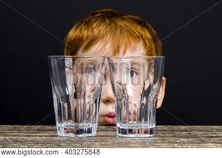 Portrait Of A Nice Boy With Red Hair Playing With Empty Glass Glasses While Cooking, A Boy Of Nice G