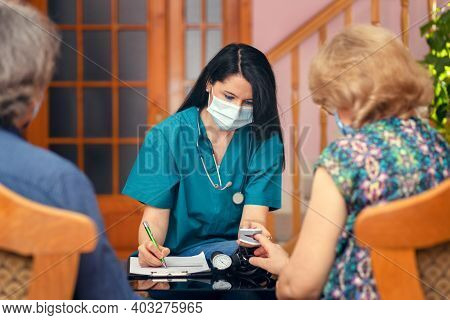 Female Nurse Doing Blood Oxygen Measurement With Pulse Oximeter To Senior People During Home Visit -