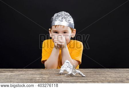A Beautiful Red-haired Boy With A Homemade Aluminum Foil Hat, A Boy Playing With A Foil Cap That Can