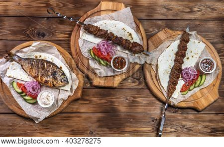 Pork Kebab, Minced Kebab On A Metal Skewer, Grilled Dorado With Sauce, Sliced Cucumbers, Tomatoes An