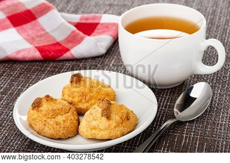 Checkered Napkin, Coconut Cookies In White Glass Saucer, Cup Of Tea, Teaspoon On Dark Mat