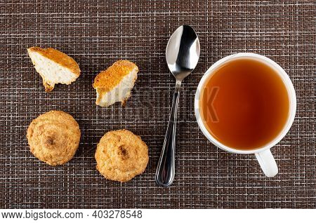 Few Coconut Cookies, Halves Of Cookies, Teaspoon, White Cup With Tea On Dark Mat. Top View