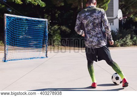 Rear View Of An Unrecognizable Football Player Kicking The Soccer Ball Into An Empty Goal In A Concr