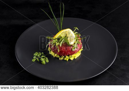 Beef Tartar With Egg Served On A Black Stone Plate. Tartar On A Black Plate With Avocado, Herbs, Sal