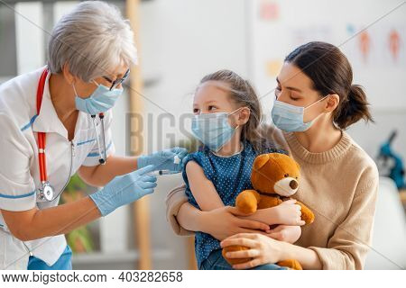 Doctor vaccinating child, kid with mother at hospital.