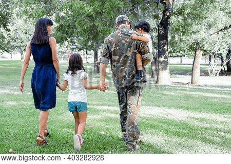Back View Of Happy Family Walking Together On Meadow In Park. Father Wearing Camouflage Uniform, Hol