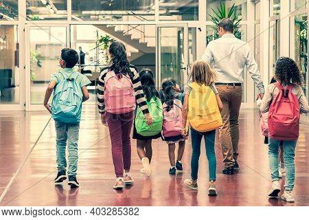 Schoolkids With Colorful Backpacks And Male Teacher Walking Through School Hallway. Back View, Full