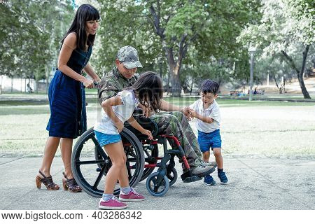 Disabled Military Father Talking With Cute Children. Caucasian Middle-aged Dad In Camouflage Uniform