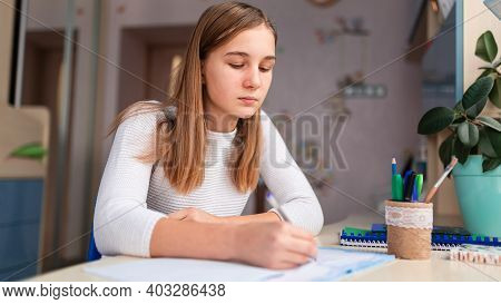 Beautiful Schoolgirl Studying At Home Doing School Homework. Distance Learning Online Education