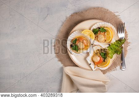Scallops With Lemon On White Background With Napkin And Fork. Baked Scallops With Caviar And Creamy