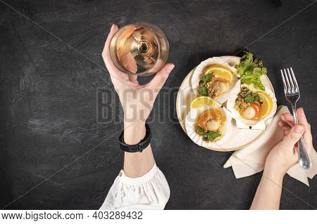 Baked Scallops With Caviar And A Glass Of Wine On A Black Background. Female Hands Hold A Glass Of W