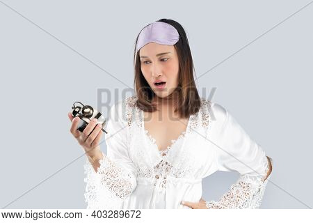 Asian Woman In A White Satin Nightgown And Wearing Lace Robe Shocked As He Wakes Up Late. A Girl Who