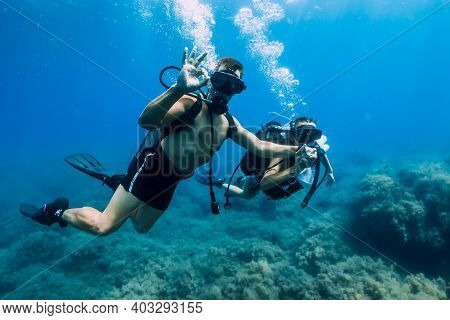 August 20, 2020. Anapa, Russia. Couple Of Scuba Divers Glides Underwater In Transparent Blue Sea. Sc